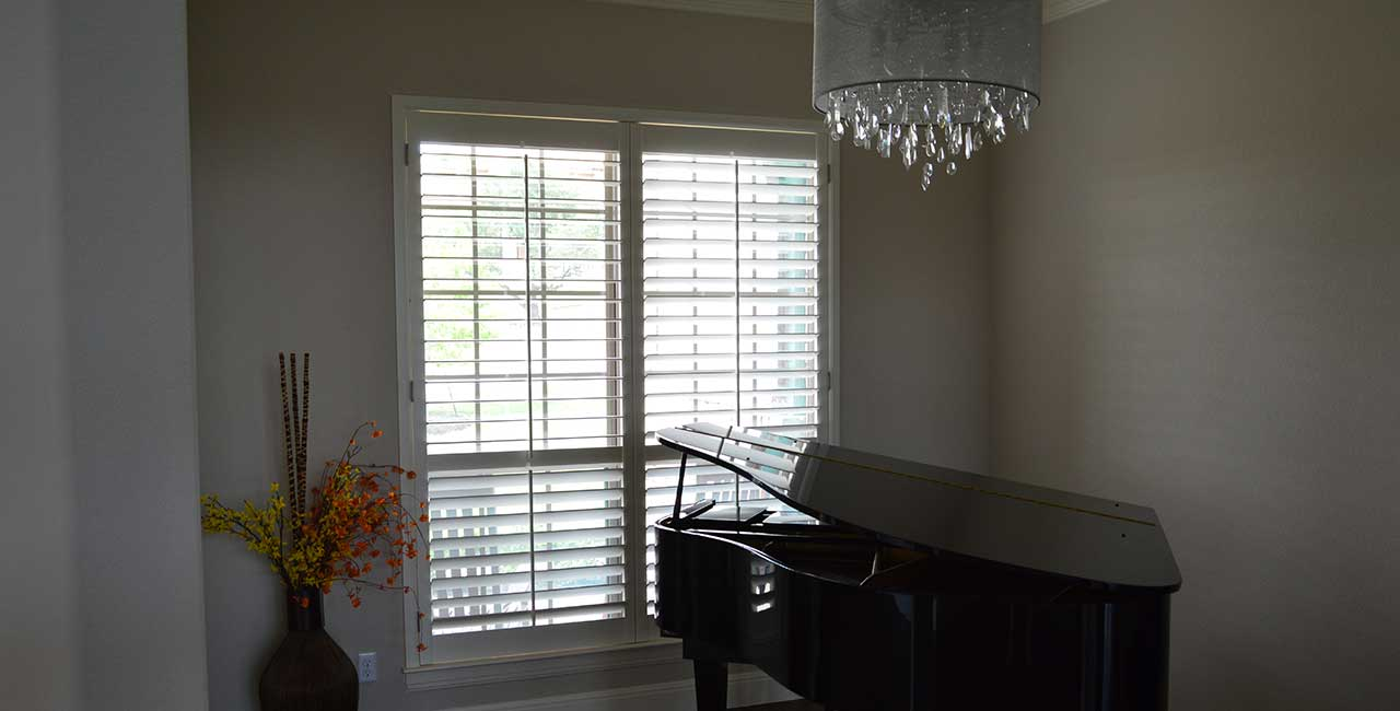 Plantation Shutters with Chandelier and Grand Piano